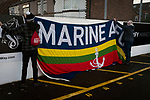 Marine 1 Hyde United 0, 12/12/2020. Marine Travel Arena, FA Trophy First Round. Two home supporters attaching a club flag to a fence before Marine play Hyde United in an FA Trophy first round tie at the Marine Travel Arena, formerly known as Rossett Park, in Crosby. Due to coronavirus regulations which had suspended league games, the Merseysiders' only fixtures were in cup competitions, including their forthcoming tie against Tottenham Hotspur in the FA Cup third round. Marine won the game by 1-0, watched by a permitted capacity of 400, with the visitors having two men sent off in the second half. Photo by Colin McPherson.