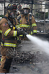 Firefighters working a scene to douse a fire in a greenhouse