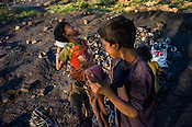 A young scavenger, Jugnu (8, right) shares a light moment inbetween collecting the coked coal in Bokapahari village in Jharia, outside of Dhanbad in Jharkhand, India.  Photo: Sanjit Das/Panos