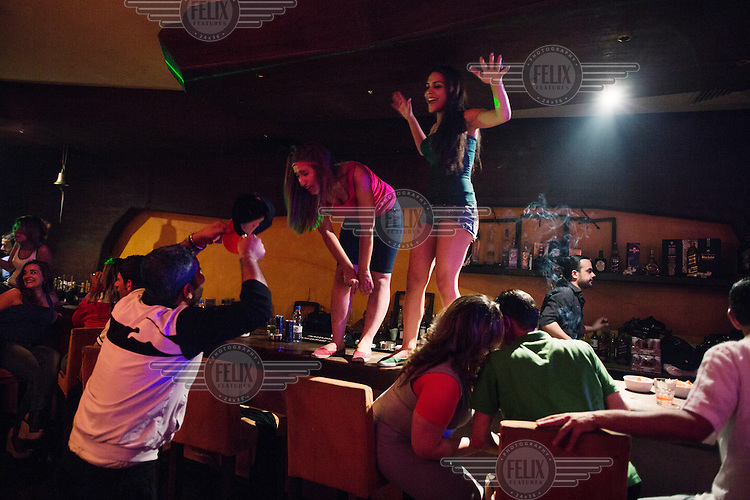 Women dame on the bar while Ismail Otaeashi sings pro-President al Assad songs during a Saturday night at the VIP Club, in Damascus, Syria.