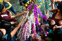 """Salvadoran girls decorate coconut palm fronds with flower blooms during the Flower & Palm Festival in Panchimalco, El Salvador, 8 May 2011. On the first Sunday of May, the small town of Panchimalco, lying close to San Salvador, celebrates its two patron saints with a spectacular festivity, known as """"Fiesta de las Flores y Palmas"""". The origin of this event comes from pre-Columbian Maya culture and used to commemorate the start of the rainy season. Women strip the palm branches and skewer flower blooms on them to create large colorful decoration. In the afternoon procession, lead by a male dance group performing a religious dance-drama inspired by the Spanish Reconquest, large altars adorned with flowers are slowly carried by women, dressed in typical costumes, through the steep streets of the town."""