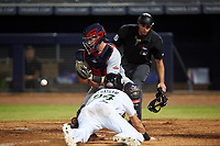 Surprise Saguaros catcher Jakson Reetz (4) prepares to apply the tag to C.J. Chatham (24) with home plate umpire Paul Clemons in position to make the call during an Arizona Fall League game against the Peoria Javelinas on September 22, 2019 at Peoria Sports Complex in Peoria, Arizona. Surprise defeated Peoria 2-1. (Zachary Lucy/Four Seam Images)