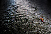 A kayaker navigates his small craft toward the shoreline in the late afternoon sun on Hoover Reservoir in Columbus, Ohio.