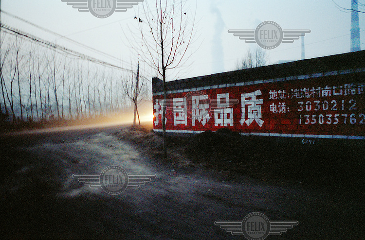 The perimeter walls of a coal-fired power station are emblazoned with an advertisement displaying the words 'International Standard' in Chinese. This particular coal power station is situated by a school in a residential area. The roads and nearby farmland of this small village are blackened with coal dust and fly ash. China is one of the world's largest producers and consumers of coke fuel. It is also one of the world's largest producers of both carbon and sulphur dioxide.