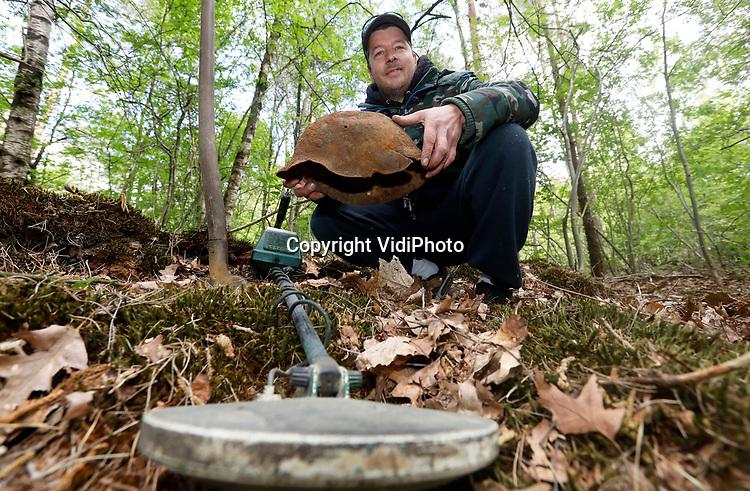 Foto: VidiPhoto<br /> <br /> ARNHEM - Detectoramateur Jeffrey Peeters (34) uit Arnhem demonstreert hoe hij met zijn metaaldetector speurt naar militaria. De Duitse helm die hij bij zich heeft is gevonden tijdens een eerdere zoektocht. Jeffrey bezit al sinds zijn vijftiende een metaaldetector en heeft al zo'n 40 Duitse helmen gevonden en honderden andere voorwerpen uit de oorlog. Een deel van zijn vondsten heeft hij geschonken aan het Arnhems Oorlogsmuseum 40-45. Het aantal detectorzoekers is sinds de coranacrisis fors gestegen.