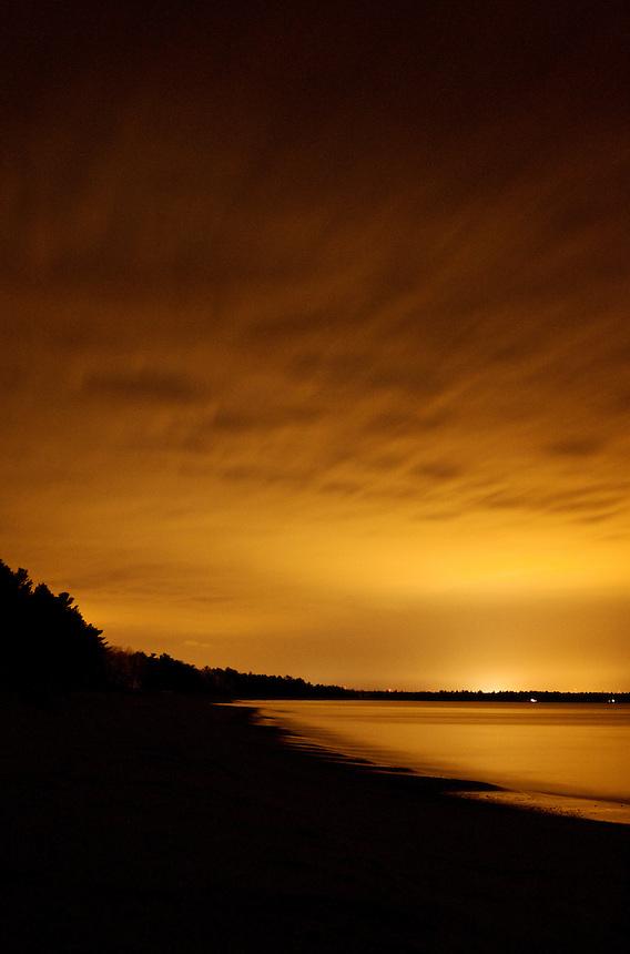 The orange glow of Marquette, MI illuminates the clouds and Lake Superior shoreline.