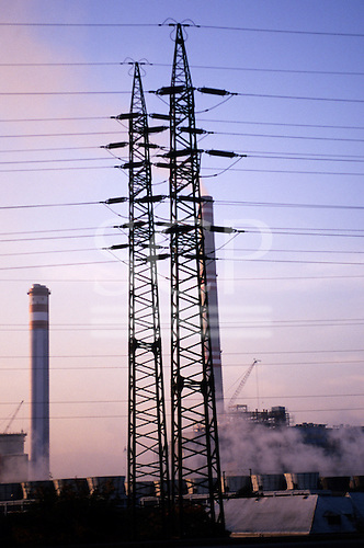 Czech Republic. High voltage electricity power line pylons and power station chimneys at sundown.