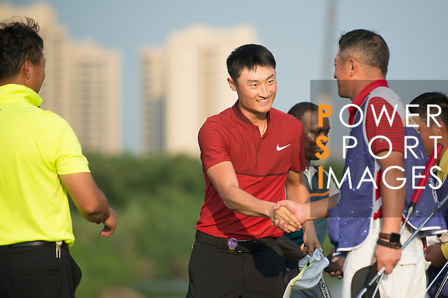 Li Haotong of China (in red) shakes hands with Zhao Hongbo (in yellow) at the end of their game during the World Celebrity Pro-Am 2016 Mission Hills China Golf Tournament on 23 October 2016, in Haikou, Hainan province, China. Photo by Marcio Machado / Power Sport Images