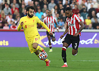 Rico Henry of Brentford takes the ball past Liverpool's Mo Salah during Brentford vs Liverpool, Premier League Football at the Brentford Community Stadium on 25th September 2021