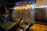 "A Colombian sign painter takes down a just-finished music party poster in the sign painting workshop in Cartagena, Colombia, 17 April 2018. Hidden in the dark, narrow alleys of Bazurto market, a group of dozen young men gathered around José Corredor (""Runner""), the master painter, produce every day hundreds of hand-painted posters. Although the vast majority of the production is designed for a cheap visual promotion of popular Champeta music parties, held every weekend around the city, Runner and his apprentices also create other graphic design artworks, based on brush lettering technique. Using simple brushes and bright paints, the artisanal workshop keeps the traditional sign painting art alive."