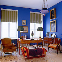 In a St Petersburg living room the warmth of deep-blue walls is the perfect foil for a collection of antique furniture