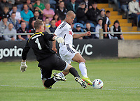 Pictured: Casey Thomas of Swansea (R) challenged by Kristian Rogers goalkeeper for Port Talbot (L). Saturday 17 July 2011<br />