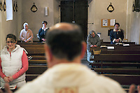 Switzerland. Canton Ticino. Corippo lies in the Verzasca valley. Anita Gaggetta (left), Clarina Scettrini (back left), Daniela Ronzoni( back center), Marco Castelli (catholic priest), Gabriela Scettrini (center right) and Pia Scettrini (right) during the evening mass. With a population of just 16, Corippo is the smallest municipality in Switzerland. Despite this, it possesses the trappings of communities many times its size such as its own coat of arms, a town council consisting of three local citizens (Pia Scettrini as vice mayor) and a village church. A town council is a democratically elected form of government for small municipalities. A council may serve as both the representative and executive branch. The village has maintained its status as an independent entity since its incorporation in 1822. 8.05.13 © 2013 Didier Ruef