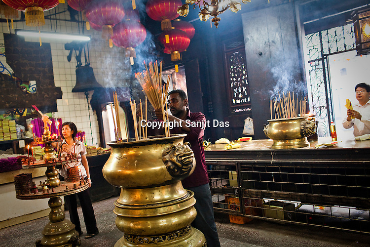 A devout Chinese devotee prays while an Indian man clears out the incense sticks at the Goddess of Mercy temple in the UNESCO heritage city of Georgetown in Penang, Malaysia. Photo: Sanjit Das/Panos
