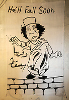 A cartoon drawing of Gaddifi on a wall in Benghazi, showing him standing on a wall, reading 'He'll Fall Soon'. On 17 February 2011 Libya saw the beginnings of a revolution against the 41 year regime of Col Muammar Gaddafi.