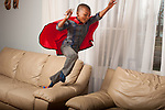 4 year old boy wearing superhero cape leaping from couch to chair holding action figure