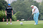 John Daly (right) hits a football with a golf club while Robbie Fowler watches during the World Celebrity Pro-Am 2016 Mission Hills China Golf Tournament on 23 October 2016, in Haikou, Hainan province, China. Photo by Weixiang Lim / Power Sport Images
