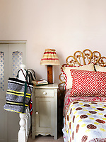 The bed in this guest bedroom has a retro wicker headboard and is covered in patterned textiles