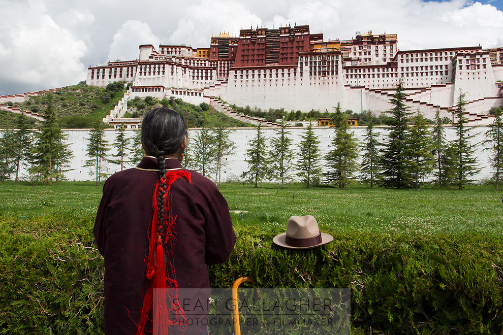 A man prays in front of the Potala Palace in Lhasa. One of the spiritual centers of Tibet, thousands of pilgrims visit each day, journeying here at least once in their lifetimes. They walk clockwise around the palace, pausing to pray and take in the sacred structure before them.