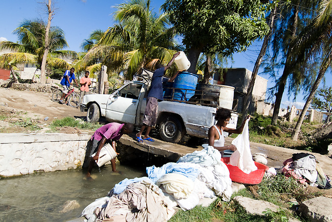 After Hurrican Ike and the following flood in September 2008 the sanitation red was highly affected. Local people from Gonaives fill up big waterbuckets on the back of their truck with water of a small river. Right next a woman wahes dirty sheets.