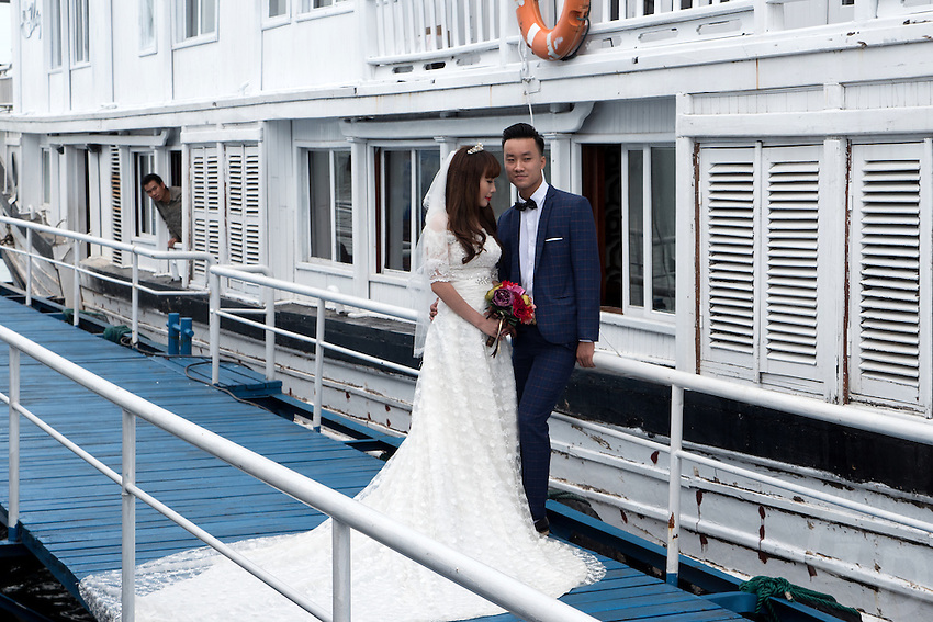This happy Couple using the Boats as props in Halong Bay for their Wedding Photos. Vietnam