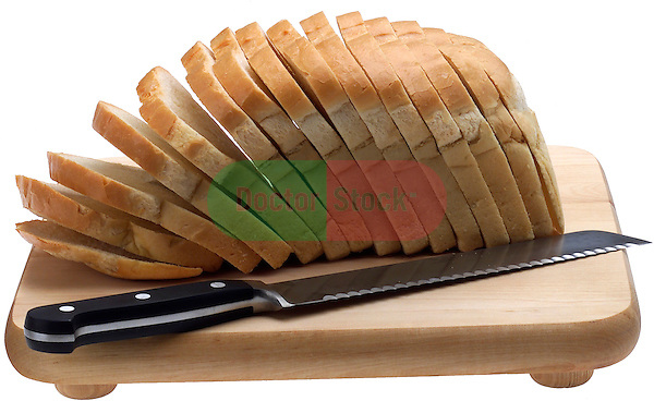 cutting board with sliced loaf of white bread and bread knife on shadowless white background