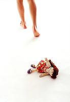 Bare legs walking away from Raggedy Ann doll<br />