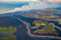 lava erupting from fissure 8 of the Kilauea Volcano east rift zone in Leilani Estates subdivision, near Pahoa, flows as a glowing river through around Green Mountain cinder cone to enter the ocean just south of Cape Kumukahi, Kapoho, Puna, Big Island, Hawaii, USA, Pacific Ocean