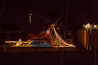 A Santa captain and a Frosty the Snowman first mate aboard a holiday decorated boat moored at the San Leandro Marina  on an evening before Christmas 2020.