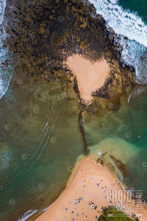 An aerial view of a heart-shaped spot of sand in Po'ipu Beach Park, Kaua'i.
