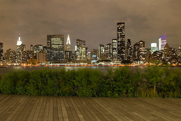 AVAILABLE FROM JEFF AS A FINE ART PRINT.<br /> <br /> AVAILABLE FOR LICENSING FROM PLAINPICTURE.  Please go to www.plainpicture.com and search for image # p5690234.<br /> <br /> Midtown Manhattan Skyline on a Cloudy and Windy Night, Viewed from Gantry Plaza State Park in Queens, New York City, New York State, USA