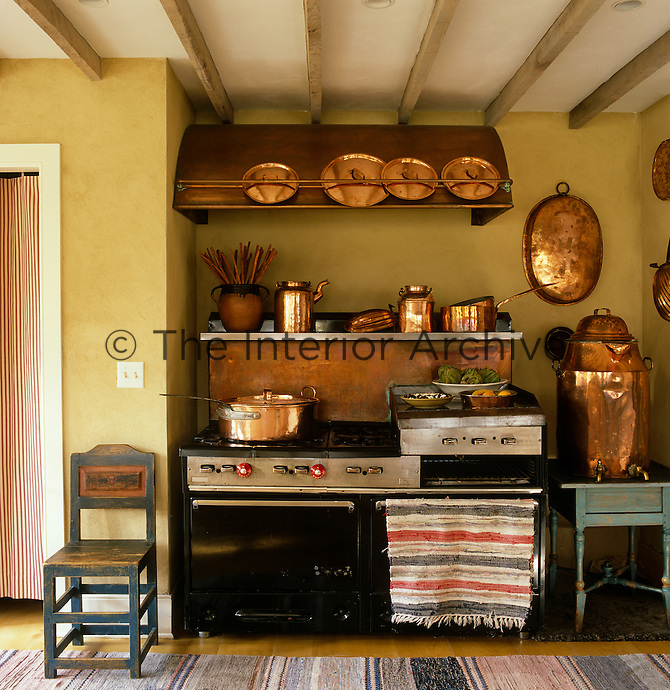 The large range in the kitchen displays a collection of Swedish copper pots