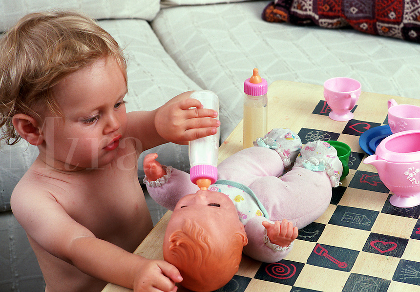 Toddler feeds a bottle to a baby doll.