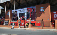 May 4th 2020, Liverpool, United Kingdom;  Anfield stadium during the suspension of the Premier League due to the Covid-19 virus pandemic;  a passer by looks through the locked and deserted Paisley Gateway entrance to the Kop