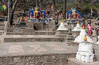 Nepal, Kathmandu, Swayambhunath.  Buddha Statues Flank the Stairs Leading to the Stupa at the top of the Hill.