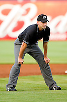Umpire Brian Miller handles the calls on the bases during the South Atlantic League game between the Kannapolis Intimidators and the Greensboro Grasshoppers at NewBridge Bank Park on May 15, 2012 in Greensboro, North Carolina.  The Grasshoppers defeated the Intimidators 11-2.  (Brian Westerholt/Four Seam Images)