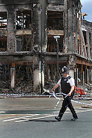 A policeman cordons off an area next to a burnt out building, destroyed during a riot in Tottenham. London saw the beginnings of riots on Saturday evening, after a peaceful protest in response to the shooting by police of Mark Duggan during an attempted arrest, escalated into violence. By the third night of violence, rioting and looting had spread to many areas of the capital and to other cities around the country.