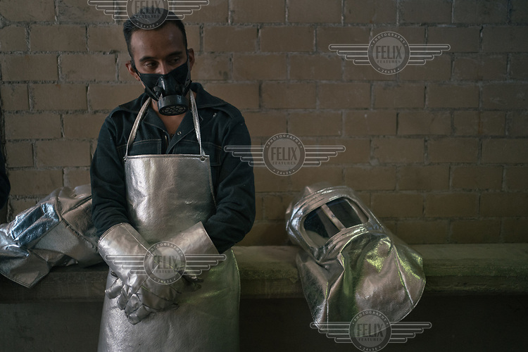 Victor Manuel Cruz Ramos (29), an employee who works in the crematorium at a public cemetery, rests beside his personal protective equipment (ppe) after cremating the body of a person who died of suspected COVID-19. Ramos, and his cousin who is also employed at the site, had just worked for twenty days without pause to try and cope with the increasing number of coronavirus victims.