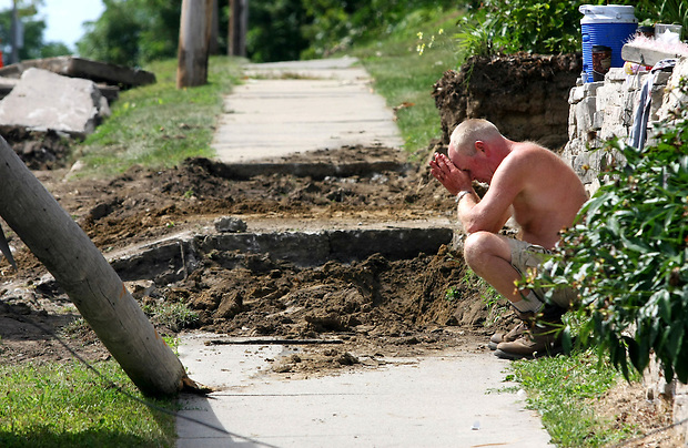 Paul Maple, 57, of Johnston, crouches at the scene of an accident near the intersection of SW 26th and Watrous Avenue in Des Moines.  He was performing concrete work when the skid-steer loader he was driving knocked over the utility pole at left, striking his coworker, who later died from his injuries.