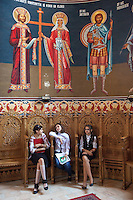 """Romania. Iași County. Iasi. Three gossiping girls seated on wooden chairs and three saints in the orthodox church """"Saint Nektarios"""". Iași (also referred to as Iasi, Jassy or Iassy) is the largest city in eastern Romania and the seat of Iași County. Located in the Moldavia region, Iași has traditionally been one of the leading centres of Romanian social, cultural, academic and artistic life. The city was the capital of the Principality of Moldavia from 1564 to 1859, then of the United Principalities from 1859 to 1862, and the capital of Romania from 1916 to 1918. 6.06.15 © 2015 Didier Ruef"""