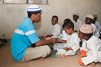 Zanzibar, Tanzania.  Imam in a Madrassa (Koranic School)  Teaching Young Boy to Read Letters of the Arabic Alphabet.