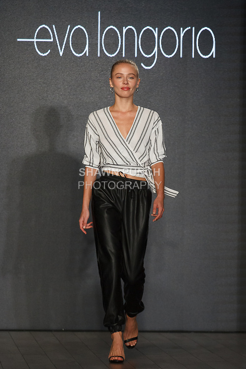 Model walks runway in a rayon crepe stripe wrap blouse and plush faux leather track pant, from the Eva Longoria Spring 2018 collection for Style 360 NYFW at Metropolitan West on 639 West 46 Street, September 13 2017, during New York Fashion Week.