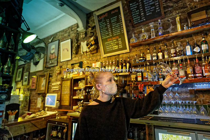 Pictured: A female bartender checks a wine glass behind the counter at Noah's Yard bar in the Uplands area of Swansea, Wales, UK. Monday 30 November 2020<br /> Re: Pubs and restaurants will have to stop serving alcohol shut at 6pm from this Friday due to the Covid-19 Coronavirus pandemic, Wales, UK.