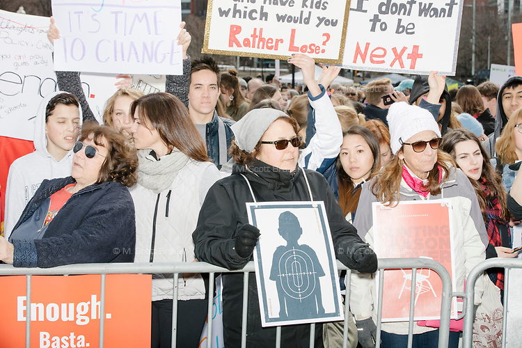 """People gather during the March For Our Lives protest and demonstration in Boston Common in Boston, Massachusetts, USA, on Sat., March 24, 2018. The march was held in response to recent school gun violence. Here signs read """"It's time to change,"""" """"I don't want to be next"""" and """"Enough. / Basta."""""""