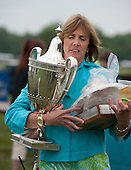 Co-race chair Carrington Price lugs the Queens Cup and other hardware after the races.