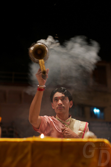 """At the ghats of Varanasi Hindu devotees performing the """"Puja"""" with lighted lamps Varanasi Ganges India"""