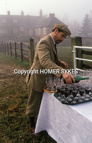 Nether Worton, Oxfordshire. 1991<br /> Wearing the estate tweed a Schuster family factor, down from their  Scottish Glen Kinglas estate, pours the stirrup cup, a birthday celebratory drink for the Hon Mrs Lorna Schuster before the off.