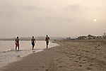 Three boys walk along the beach early in the morning in Muscat. Oman - National Geographic Traveler