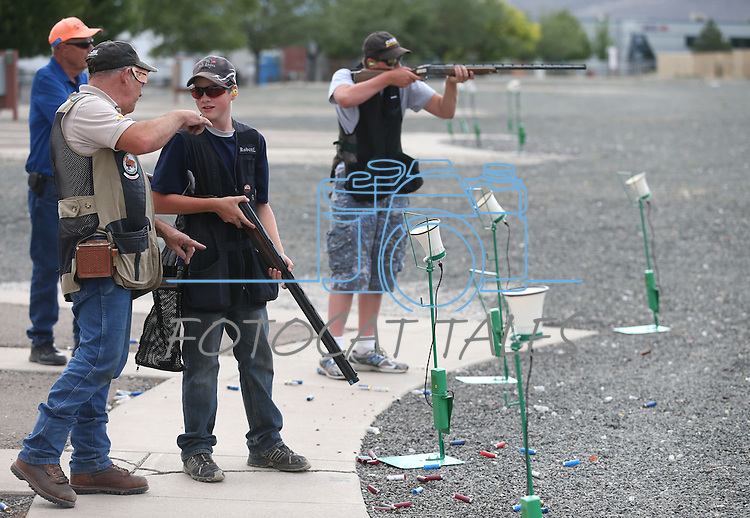 Coaches Greg and Rusty Wolbers work with Robert Lamkin and Weston Swift, both 13, during practice at the Capital City Gun Club, in Carson City, Nev., on Friday, July 11, 2014.<br /> Photo by Cathleen Allison