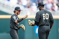 Vanderbilt Commodores third baseman Austin Martin (16) hand the ball to pitcher Kumar Rocker (80) during Game 8 of the NCAA College World Series against the Mississippi State Bulldogs on June 19, 2019 at TD Ameritrade Park in Omaha, Nebraska. Vanderbilt defeated Mississippi State 6-3. (Andrew Woolley/Four Seam Images)
